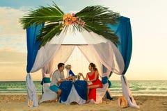 Le giovani belle coppie hanno una cena romantica al tramonto su un tro Fotografie Stock Libere da Diritti