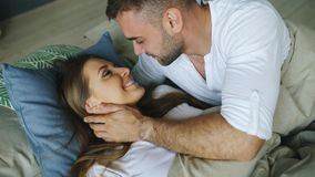 Le giovani belle e coppie amorose svegliano alla mattina Il bacio attraente dell'uomo ed abbraccia la sua moglie a letto fotografia stock