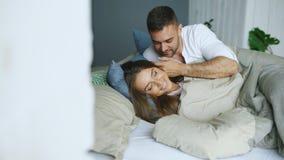 Le giovani belle e coppie amorose svegliano alla mattina Il bacio attraente dell'uomo ed abbraccia la sua moglie a letto immagini stock libere da diritti