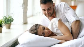 Le giovani belle e coppie amorose svegliano alla mattina Il bacio attraente dell'uomo ed abbraccia la sua moglie a letto immagini stock