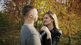 Le giovani coppie ad una data in autunno parcheggiano stock footage