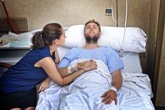 Le giovani coppie alla stanza di ospedale equipaggiano la menzogne a letto donna preoccupata che tiene suo preoccuparsi della man immagine stock