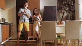 Le giovani coppie allegre attraenti si divertono ballare cantano la canzone mentre cucinano nella cucina nella mattina soleggiata stock footage