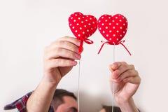 Le giovani coppie amorose che si tengono per mano il simbolo rosso dei cuori amano il giorno del ` s del biglietto di S. Valentin Fotografia Stock