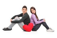 Le giovani coppie amorose e un cuore rosso hanno modellato il cuscino Fotografie Stock