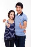 Le giovani coppie asiatiche mostrano i pollici isolati su fondo bianco. Immagine Stock