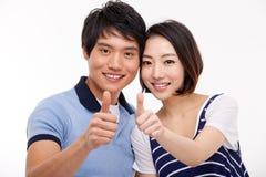 Le giovani coppie asiatiche mostrano i pollici isolati su fondo bianco. Fotografie Stock