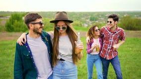 Le giovani coppie belle cammina nel parco, tenente le bottiglie con le bevande video d archivio