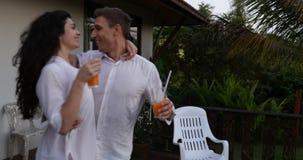 Le giovani coppie camminano fuori sul terrazzo che si tiene per mano la conversazione al tramonto, all'uomo felice ed all'abbracc stock footage