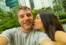 Le giovani coppie caucasiche asiatiche miste felici ed attraenti di etnia nell'amore che prende il selfie rappresentano insieme s immagini stock
