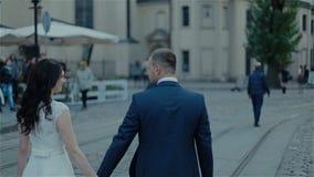 Le giovani coppie che camminano sulla città hanno preso la mano stock footage