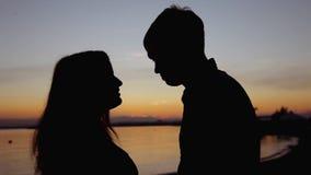 Le giovani coppie che fanno il cuore modellano con le armi sulla spiaggia contro il tramonto dorato video d archivio
