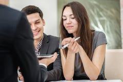Le giovani coppie che si siedono ad una tavola e risolvono il loro problemi con la a Immagine Stock