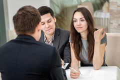 Le giovani coppie che si siedono ad una tavola e risolvono il loro problemi con la a Immagini Stock
