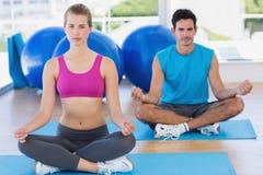 Le giovani coppie che si siedono nel loto posture allo studio di forma fisica fotografia stock
