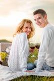 Le giovani coppie che si siedono su un picnic con il canestro e la bevanda bianchi vincono Fotografie Stock Libere da Diritti