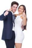 Le giovani coppie che sorridono con i pollici aumentano il gesto Fotografie Stock Libere da Diritti