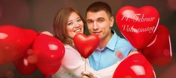 Le giovani coppie con cuore hanno modellato i palloni rossi vicino alla parete grigia fotografie stock