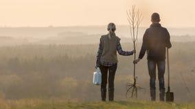 Le giovani coppie con una piantina dell'albero e una pala stanno stando vicino in un posto pittoresco fotografie stock libere da diritti