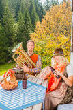 Le giovani coppie in costume bavarese tradizionale al partito su un'estate pascolano nelle montagne Fotografia Stock