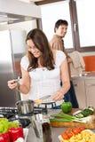 Le giovani coppie cucinano in cucina moderna Fotografia Stock Libera da Diritti