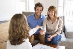 Le giovani coppie dei proprietari ricevono le chiavi della loro nuova casa immagini stock libere da diritti
