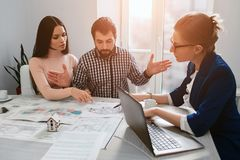 Le giovani coppie della famiglia acquistano il bene immobile della proprietà di affitto Agente che dà consultazione all'uomo ed a Immagine Stock