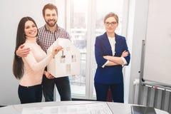 Le giovani coppie della famiglia acquistano il bene immobile della proprietà di affitto Agente che dà consultazione all'uomo ed a Fotografie Stock