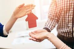 Le giovani coppie della famiglia acquistano il bene immobile della proprietà di affitto Agente che dà consultazione all'uomo ed a Fotografia Stock