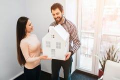 Le giovani coppie della famiglia acquistano il bene immobile della proprietà di affitto Agente che dà consultazione all'uomo ed a Immagini Stock Libere da Diritti