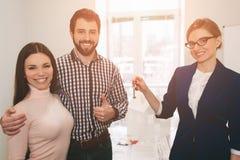 Le giovani coppie della famiglia acquistano il bene immobile della proprietà di affitto Agente che dà consultazione all'uomo ed a Immagine Stock Libera da Diritti