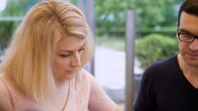 Le giovani coppie della famiglia con il bambino stanno mangiando fuori in caffè nel giorno di estate Chiuda su dell'uomo bello e  stock footage
