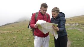 Le giovani coppie divertenti perse dei turisti sull'avventura scattano in montagna che studia insieme la mappa soffiata da vento  stock footage