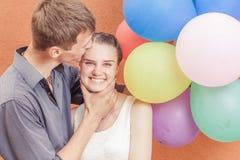 Le giovani coppie divertenti vicino alla parete arancio stanno con i palloni Fotografia Stock