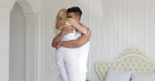 Le giovani coppie felici abbracciano la donna funzionata e saltano sopra la camera da letto domestica moderna dell'uomo archivi video
