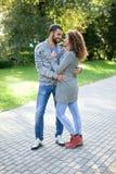 Le giovani coppie felici che camminano nel parco hanno abbracciato le giovani coppie in Immagine Stock Libera da Diritti