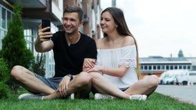 Le giovani coppie felici che esaminano lo smartphone, hanno video chiamata, chiamando gli amici o i parenti, media sociali video d archivio