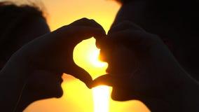 Le giovani coppie felici che fanno il cuore modellano con le mani all'oceano al tramonto Siluetta dell'uomo e della donna sopra i video d archivio