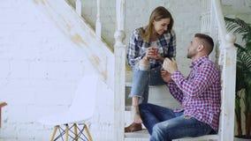 Le giovani coppie felici ed amorose bevono il tè e la conversazione mentre si siedono sulle scale in salone a casa immagini stock