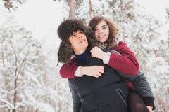 Le giovani coppie felici in inverno parcheggiano avere divertimento Fotografie Stock Libere da Diritti