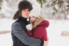 Le giovani coppie felici in inverno parcheggiano avere divertimento Immagine Stock Libera da Diritti