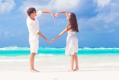 Le giovani coppie felici nel cuore di fabbricazione bianco modellano sulla spiaggia tropicale honeymoon Immagini Stock