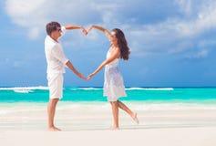 Le giovani coppie felici nel cuore di fabbricazione bianco modellano sulla spiaggia tropicale honeymoon Fotografia Stock