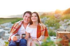 Le giovani coppie felici nell'amore all'estate fanno un picnic Immagine Stock Libera da Diritti