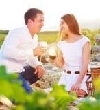 Le giovani coppie felici nell'amore all'estate fanno un picnic Immagini Stock