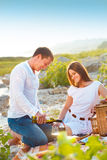 Le giovani coppie felici nell'amore all'estate fanno un picnic Immagine Stock