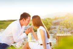 Le giovani coppie felici nell'amore all'estate fanno un picnic Fotografia Stock