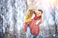 Le giovani coppie felici nell'inverno parcheggiano la risata e divertiresi Famiglia all'aperto immagini stock