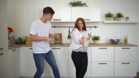 Le giovani coppie felici recentemente wed il dancing che ascolta la musica nella mattina d'uso del caffè dei pigiami della cucina stock footage