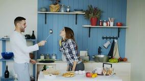 Le giovani coppie felici si divertono il dancing ed il canto nella cucina mentre ascoltano la musica di mattina a casa archivi video